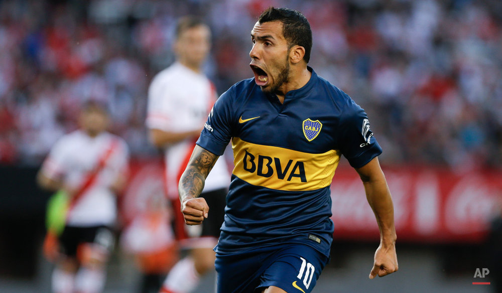 In this Sept. 13, 2015, photo, Carlos Tevez of Boca Juniors celebrates a goal scored by teammate Nicolas Lodeiro against River Plate during a local tournament soccer match in Buenos Aires, Argentina, Sunday.(AP Photo/Natacha Pisarenko)