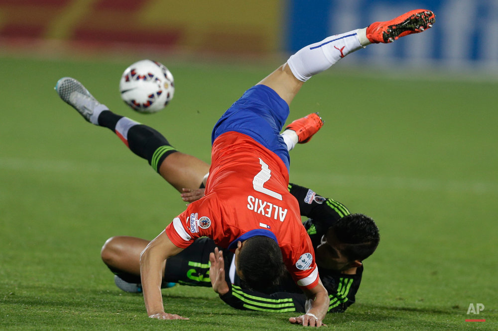 In this June 15, 2015, photo, Chile's Alexis Sanchez falls over Mexico's Carlos Salcedo, bottom, during a Copa America Group A soccer match at El Nacional stadium in Santiago, Chile. The match ended in a 3-3 draw. (AP Photo/Natacha Pisarenko)
