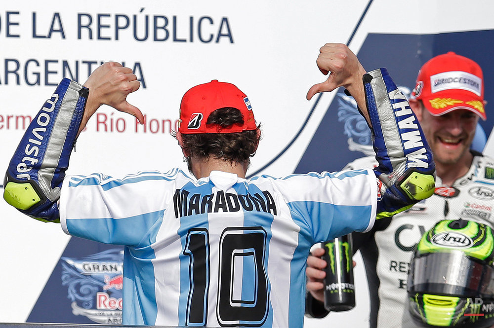 In this April 19, 2015, photo, wearing a jersey of the Argentine national soccer team with the name and number 10 of Diego Armando Maradona, Italy's Valentino Rossi celebrates on the podium after winning the MotoGP race of the Argentina's Motorcycle Grand Prix at the Termas de Rio Hondo circuit in Argentina. (AP Photo/Natacha Pisarenko)