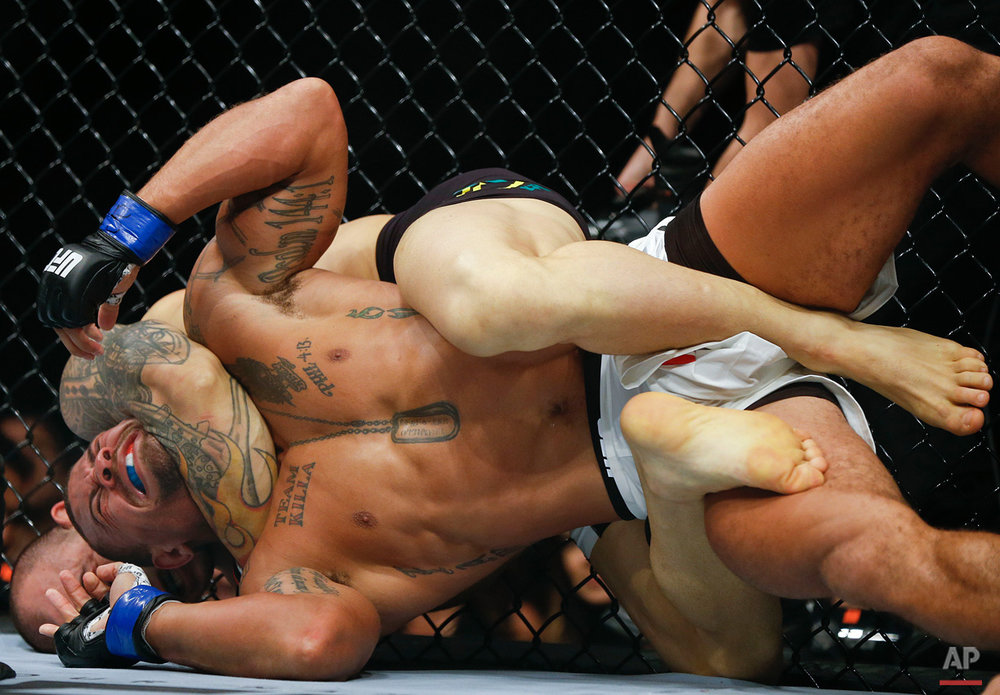 In this Nov. 8, 2015, photo, Gleison Tibau, from Brazil, back, chokes Abel Trujillo, from the United States, during their UFC lightweight mixed martial arts bout in Sao Paulo, Brazil. (AP Photo/Andre Penner)