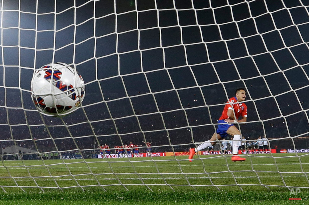 In this July 4, 2015, photo, Chile's Alexis Sanchez celebrates after scoring the winning penalty kick against Argentina during the Copa America final soccer match at the National Stadium in Santiago, Chile. Chile became Copa America champions for the first time after it defeated Argentina in a penalty shootout. (AP Photo/Ricardo Mazalan)