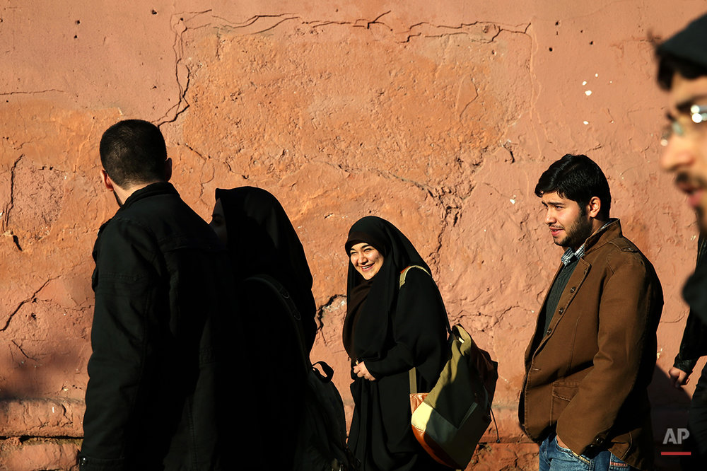 Iranians make their way at the sidewalk of  Enghelab-e-Eslami (Islamic Revolution) St. in Tehran, Iran, Tuesday, Dec. 8, 2015. (AP Photo/Ebrahim Noroozi)