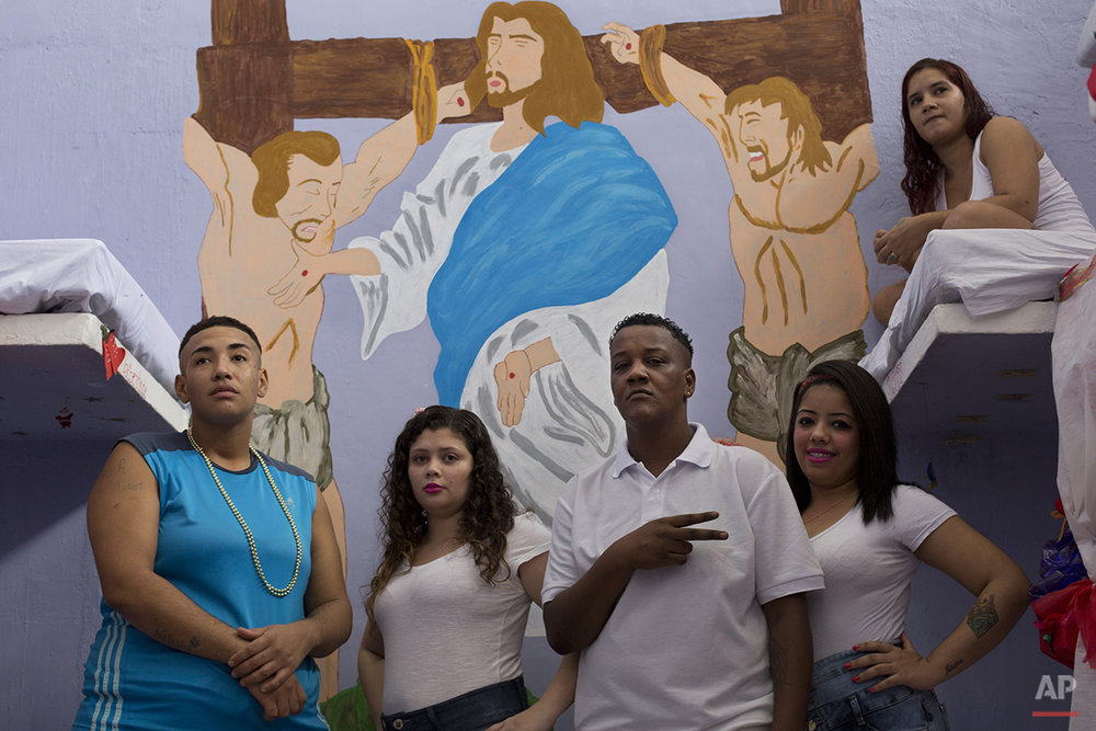 Prisoners stand in front a painting of Jesus before a Christmas decorating contest inside their cell at the Nelson Hungria prison in Rio de Janeiro, Brazil, Thursday, Dec. 10, 2015.  Inmates, overwhelming black and mixed-race women who are serving time for offenses from burglary to homicide, spent weeks decking out the cell blocks with holiday decorations they made themselves from the objects they have access to behind bars.(AP Photo/Silvia Izquierdo)