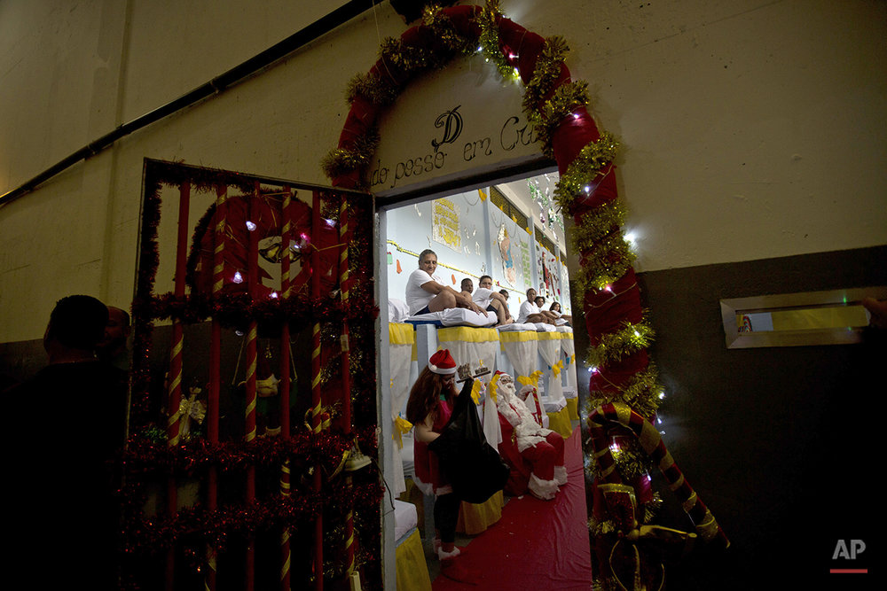 Prisoners inside sit in their cell during a Christmas decorating contest at the Nelson Hungria prison in Rio de Janeiro, Brazil, Thursday, Dec. 10, 2015.  Inmates, overwhelming black and mixed-race women who are serving time for offenses from burglary to homicide, spent weeks decking out the cell blocks with holiday decorations they made themselves from the objects they have access to behind bars. (AP Photo/Silvia Izquierdo)