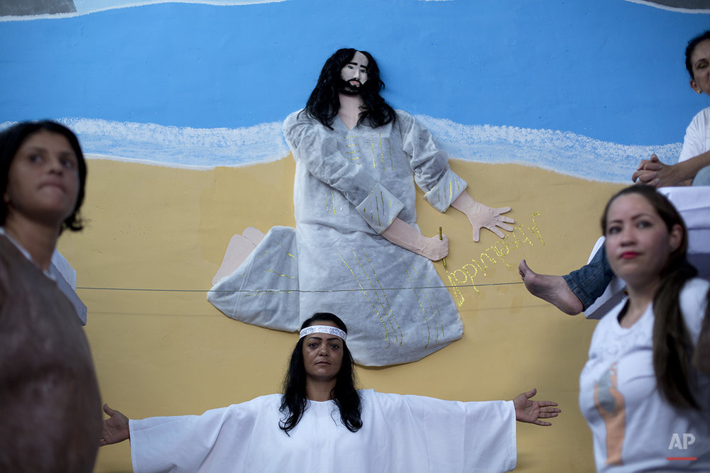 "Prisoners stand in front a painting of Jesus, that has real hair donated by a prisoner, and the word ""Acquitted"" written in Portuguese, after performing in a Christmas decorating contest inside their cell at the Nelson Hungria prison in Rio de Janeiro, Brazil, Thursday, Dec. 10, 2015.  Inmates, overwhelming black and mixed-race women who are serving time for offenses from burglary to homicide, spent weeks decking out the cell blocks with holiday decorations they made themselves from the objects they have access to behind bars. (AP Photo/Silvia Izquierdo)"