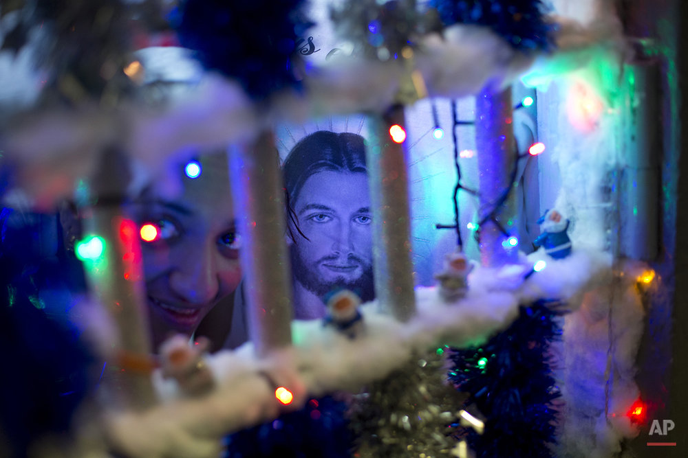 A prisoner looks through the bars of her cell during a Christmas decorating contest at the Nelson Hungria prison in Rio de Janeiro, Brazil, Thursday, Dec. 10, 2015. Each cell of 50 women or more also put on a skit dramatizing Biblical stories, with many depictions of Jesus' life, as well as David and Goliath and Daniel in the lions' den, giving prison's would-be thespians their chance to shine. Voices soared in rapture with the religious songs, and many, many tears were shed. (AP Photo/Silvia Izquierdo)