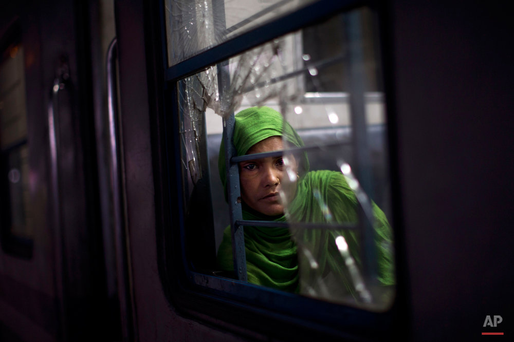 In this Wednesday, Feb. 25, 2015, photo, an Indian woman watches from a broken window of a local train at a railway station in New Delhi, India. India's national railways system, which is one of the world's largest, serves more than 23 million passengers a day. (AP Photo/Bernat Armangue)