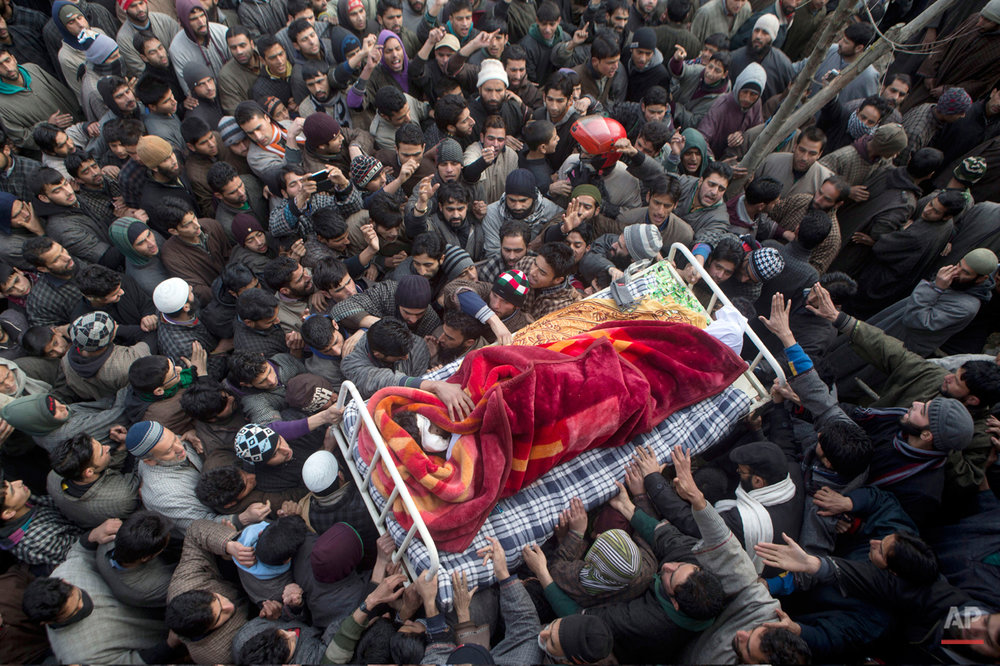 In this Friday, Jan. 16, 2015 photo, Kashmiri Muslim villagers carry the body of Ishfaq Ahmed Malik, a suspected local militant during his funeral procession in Arwani, some 55 kilometers (35 miles) south of Srinagar, India. Indian soldiers and police killed five suspected rebels during a fierce gun battle Thursday in the disputed Himalayan region of Kashmir, officials said. (AP Photo/Dar Yasin)