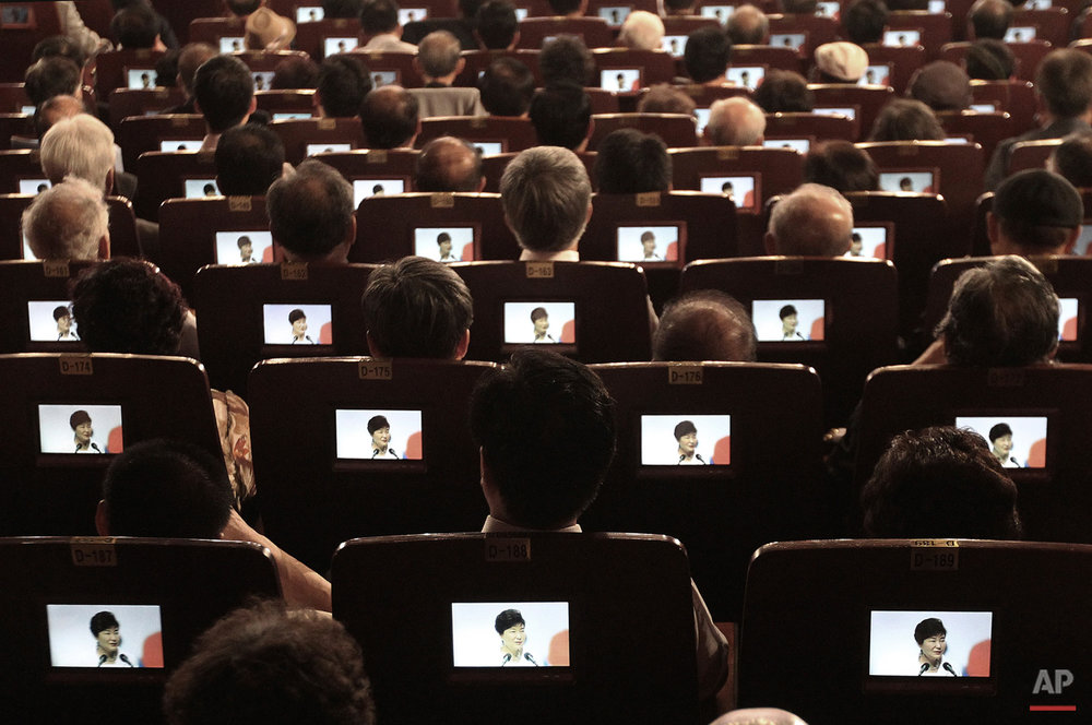 In this Saturday, Aug. 15, 2015, photo, small screens show South Korean President Park Geun-hye as participants listen to her speech during a ceremony to celebrate Korean Liberation Day from Japanese colonial rule in 1945, at Seong Cultural Center in Seoul, South Korea. (AP Photo/Ahn Young-joon)