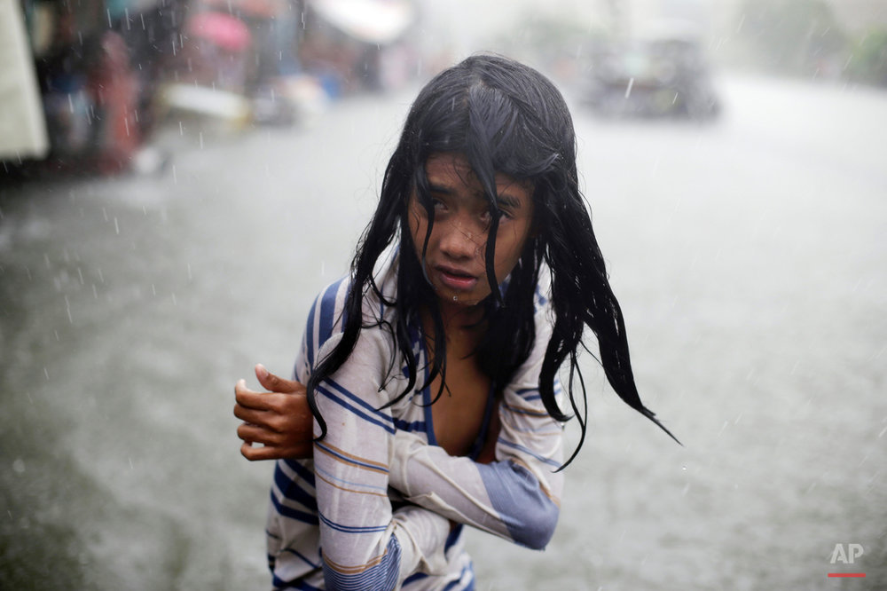 In this Wednesday, July 8, 2015, photo, a Filipino girl tries to keep herself warm as she wades through floodwaters in the coastal village of Malabon, north of Manila, Philippines. Typhoon Chan-Hom passed over the northeastern waters of the Philippines and heading to northern Taiwan on Wednesday, dumping heavy rains over the capital, Manila, and the northern provinces. (AP Photo/Aaron Favila)