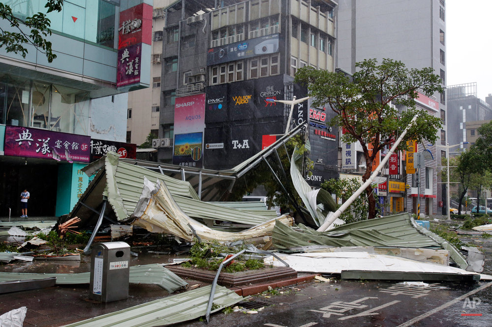 In this Aug. 8, 2015 photo, a street corner is filled with a mangled rooftop brought down by strong winds from Typhoon Soudelor in Taipei, Taiwan. Soudelor brought heavy rains and strong winds to the island Saturday with winds speeds over 170 km per hour (100 mph) and gusts over 200 km per hour (120 mph) according to Taiwan's Central Weather Bureau. (AP Photo/Wally Santana)