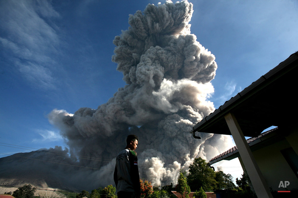 In this Thursday, June 25, 2015, photo, a man watches as Mount Sinabung releases volcanic material into the air in Tiga Serangkai, North Sumatra, Indonesia. The volcano has spewed hot lava almost daily since its alert status was raised early this month to the highest level. Thousands of villagers whose homes are in the danger zone have been evacuated to safer areas. (AP Photo/Binsar Bakkara)