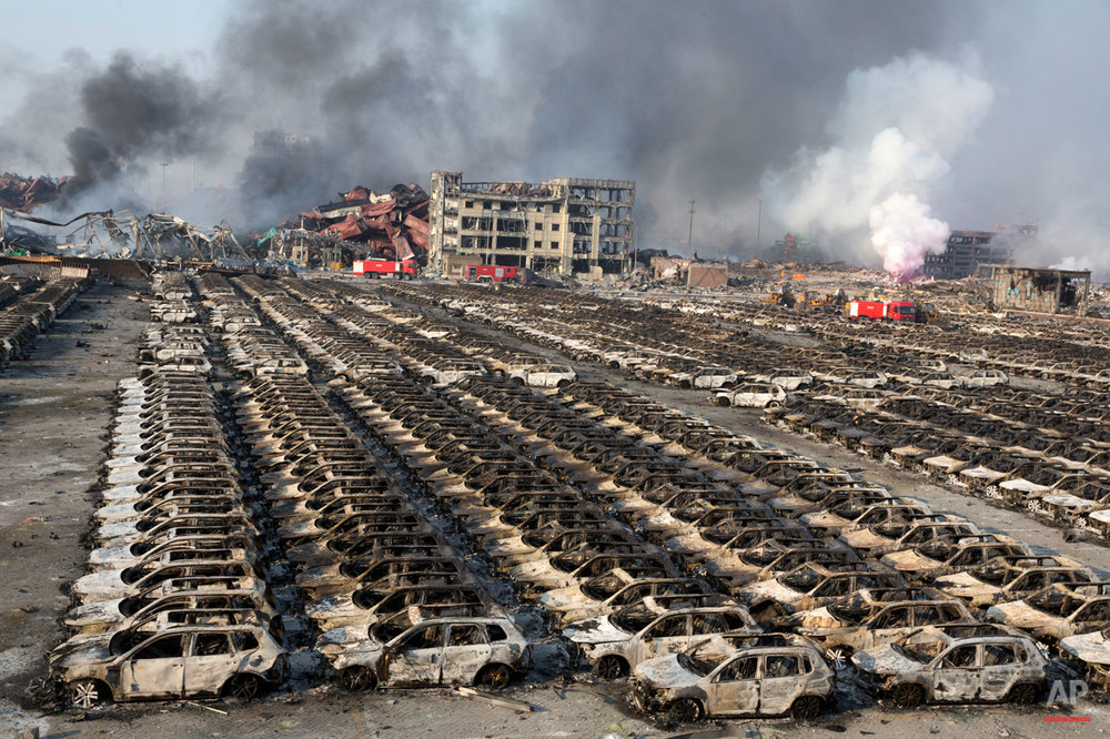 Smoke billows from the site of an explosion that reduced a parking lot filled with new cars to charred remains at a warehouse in northeastern China's Tianjin municipality, Thursday, Aug. 13, 2015. Huge explosions in the warehouse district sent up massive fireballs that turned the night sky into day in the Chinese port city of Tianjin, officials and witnesses said Thursday. (AP Photo/Ng Han Guan)