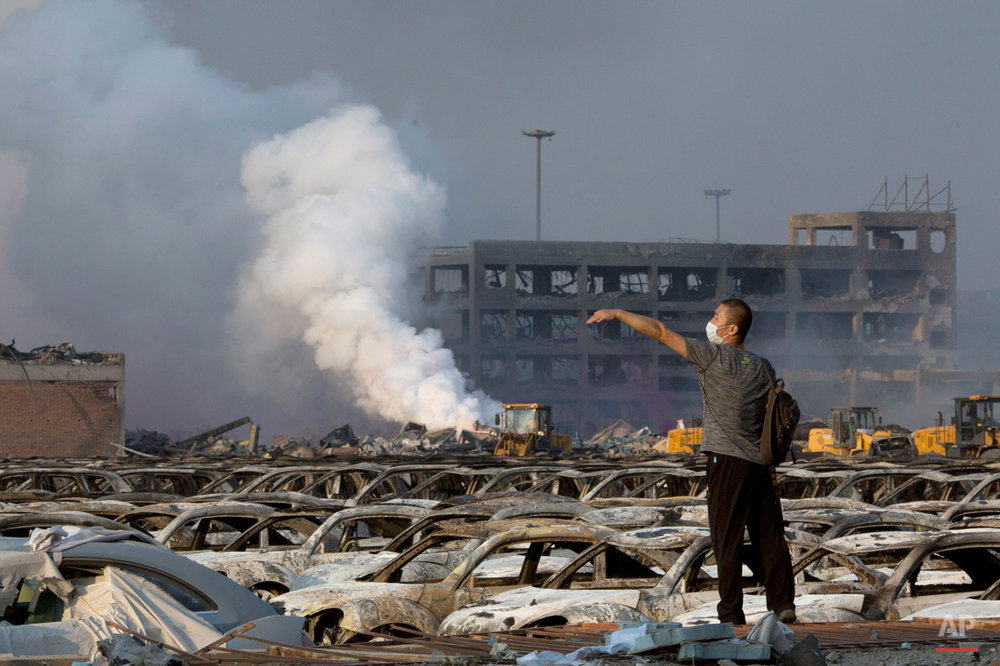In this photo taken Thursday, Aug. 13, 2015, a man walks through the site of an explosion at a warehouse in northeastern China's Tianjin municipality. Rescuers have pulled a survivor from an industrial zone about 32 hours after it was devastated by huge blasts in China???s Tianjin port. Meanwhile, authorities are moving gingerly forward in dealing with a fire still smoldering amid potentially dangerous chemicals. (AP Photo/Ng Han Guan)