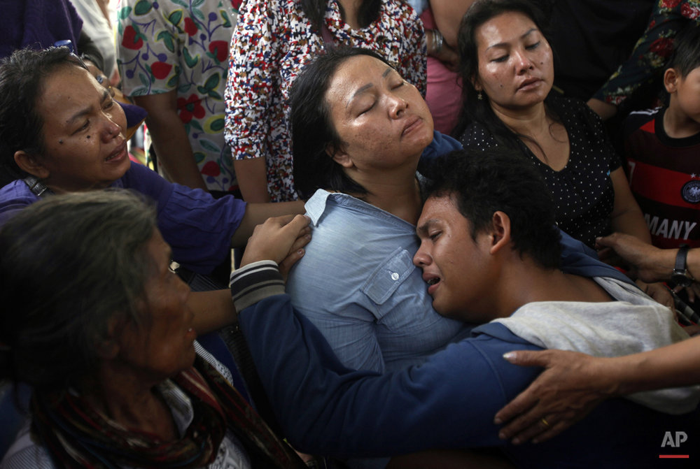 In this Wednesday, July 1, 2015, photo, family members of one of the victims of a military plane that crashed on Tuesday comfort each other at a hospital in Medan, North Sumatra, Indonesia. The C-130 Hercules crashed shortly after takeoff in the country's third largest city on June 30. (AP Photo/Binsar Bakkara)