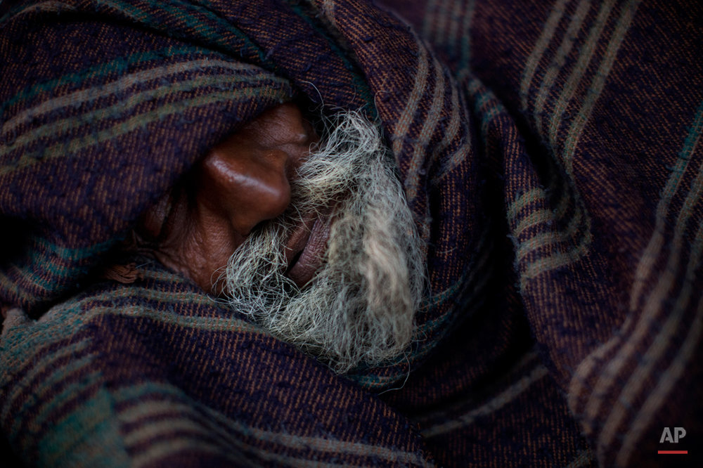 An Indian homeless man sleeps covered in a blanket early morning in the old quarters of Delhi, India, Friday, Feb. 20, 2015.  (AP Photo/Bernat Armangue)