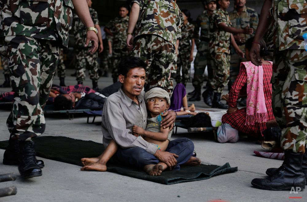 A man sits with a child on his lap as victims of Saturdayís earthquake, wait for ambulances after being evacuated at the airport in Kathmandu, Nepal, Monday, April 27, 2015. The death toll from Nepal's earthquake is expected to rise depended largely on the condition of vulnerable mountain villages that rescue workers were still struggling to reach two days after the disaster.  (AP Photo/Altaf Qadri)
