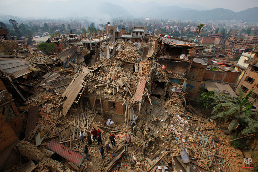 In this Sunday, April 26, 2015, photo, rescue workers remove debris as they search for victims of an earthquake in Bhaktapur near Kathmandu, Nepal. A strong magnitude earthquake shook Nepal's capital and the densely populated Kathmandu Valley before noon Saturday, causing extensive damage with toppled walls and collapsed buildings, officials said. (AP Photo/Niranjan Shrestha)