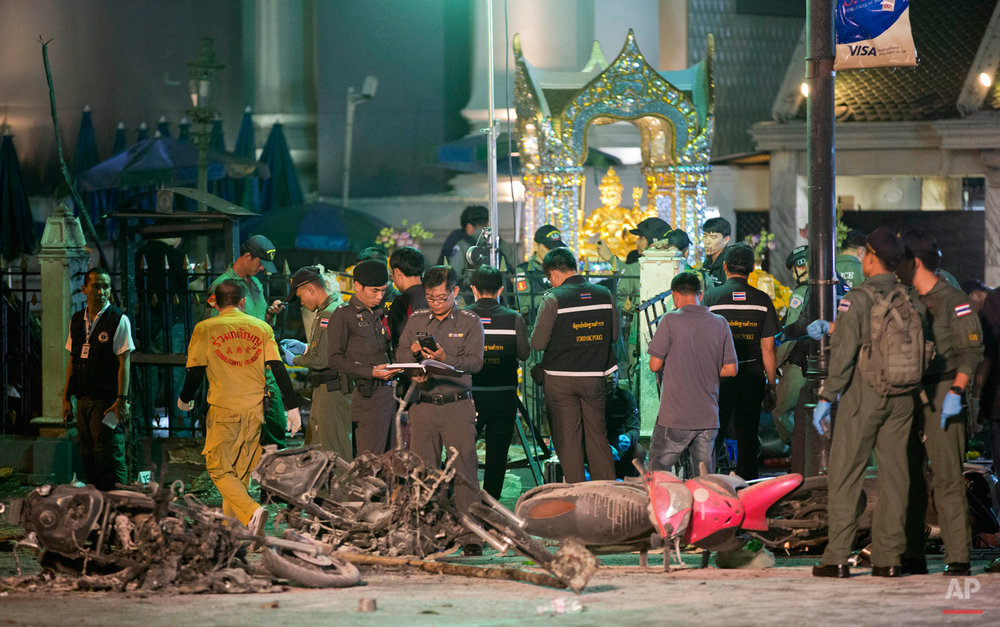 In this Aug. 17, 2015 photo, police investigate the scene at the Erawan Shrine after an explosion in Bangkok. Police in Thailand said Saturday, Sept. 26, 2015, they have gathered enough evidence to prosecute two arrested men whom they accuse of carrying out August's deadly Bangkok bombing.(AP Photo/Mark Baker)