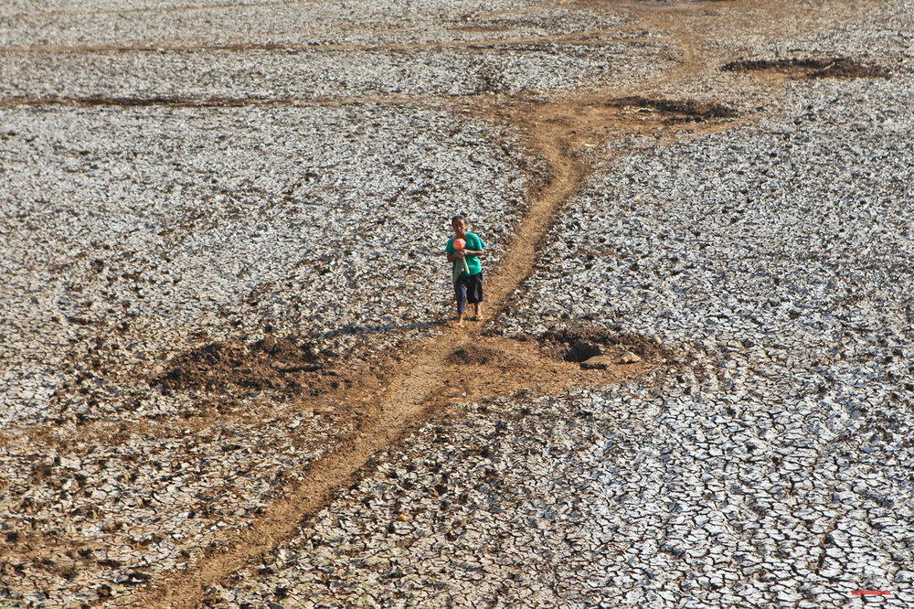 In this Saturday, Sept. 19, 2015 photo, a villager walks on a dried up dam after collecting some water in Rongkop, central Java, Indonesia. Several areas on the densely populated island of Java have been hit by drought during this dry season, forcing villagers to walk long distances to find clean water. (AP Photo/Trisnadi)