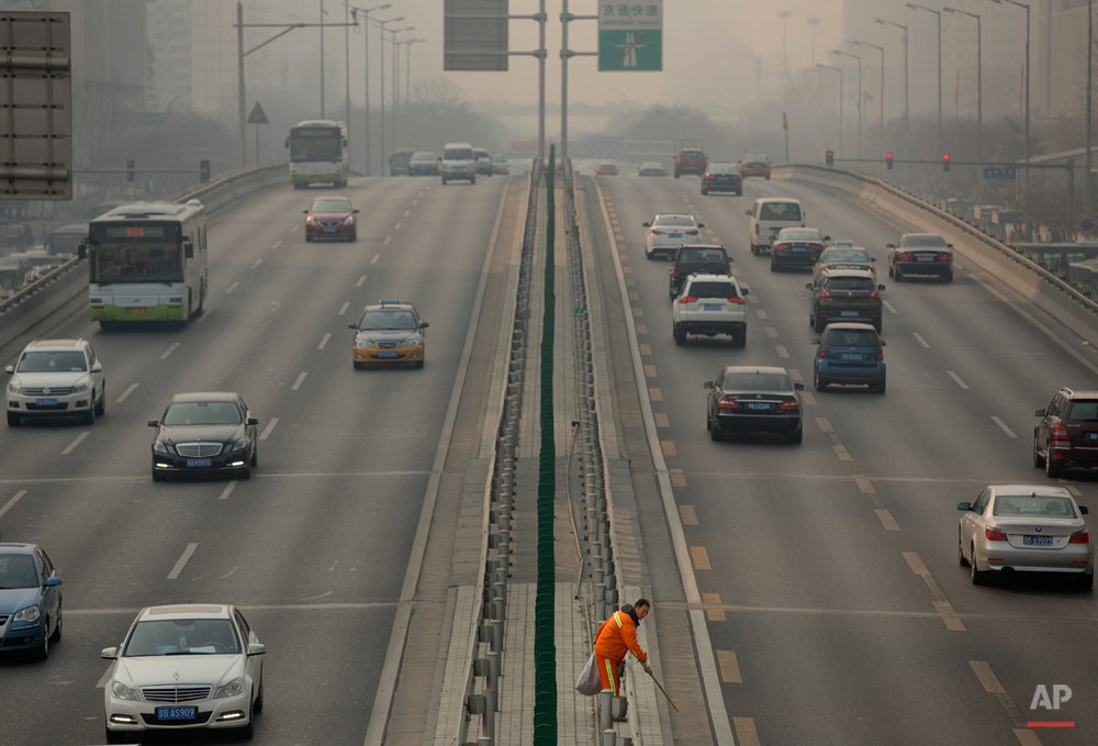 In this March 6, 2015, photo, a road worker picks up trash along the median of a highway on a smoggy day in Beijing. Chen Jining, China's minister of Environmental Protection, held a press conference on Saturday to talk about the country's efforts to fight pollution. (AP Photo/Mark Schiefelbein)