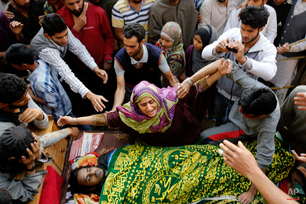 In this Oct. 5, 2015 photo, a Kashmiri Muslim woman wails near the body of a suspected rebel, during his funeral at Barhama, 40 kilometers (25 miles) south of Srinagar, Indian controlled Kashmir, Monday, Oct. 5, 2015. At least four Indian army soldiers and three suspected rebels were killed in three separated gun battles in Indian-controlled Kashmir, police said on Monday. (AP Photo/Mukhtar Khan)