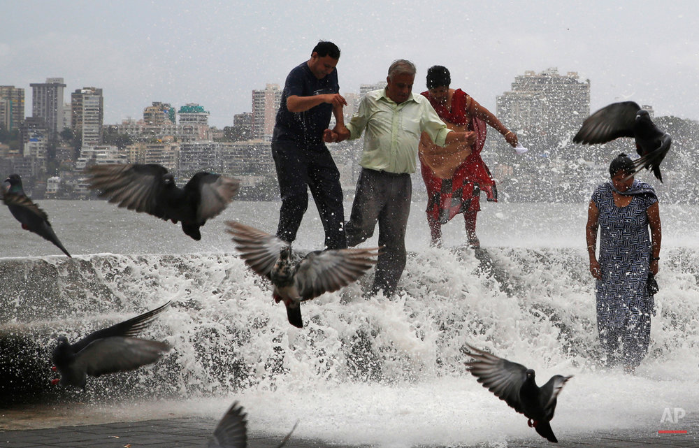 People are doused by waves crashing on the Arabian Sea shore marking the arrival of monsoon season in Mumbai, India, Tuesday, June 16, 2015. The annual rains which usually hit India from June to September are crucial for farmers whose crops feed hundreds of millions of people. (AP Photo/Rajanish Kakade)