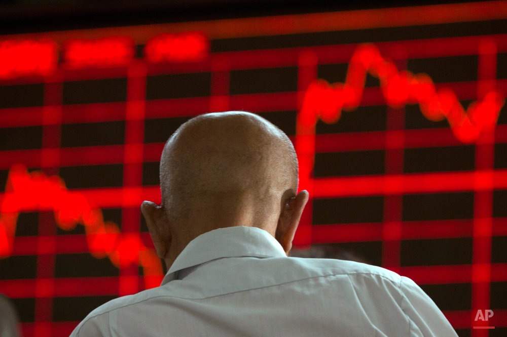 In this Aug. 26, 2015, photo, a Chinese investor monitors stock prices at a brokerage in Beijing. Asian stocks were mixed Wednesday and Shanghai's index fell despite Beijing's decision to cut a key interest rate to help stabilize gyrating financial markets and counter short liquidity. (AP Photo/Ng Han Guan)