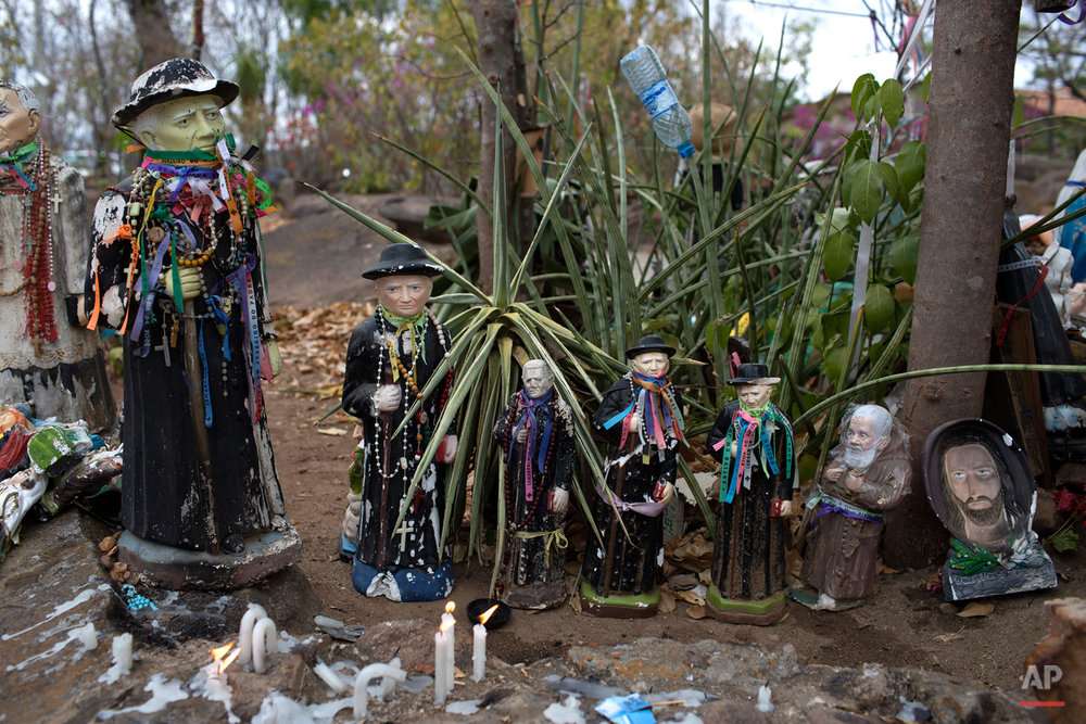 In this Oct. 31, 2015 photo, statues of Padre Cicero stand at the start of a path called the Holy Sepulcher, used by pilgrims who come to honor the late priest in Juazeiro do Norte, Brazil. The Brazilian man was both a priest and a politician, serving as mayor of the town for 15 years. (AP Photo/Leo Correa)