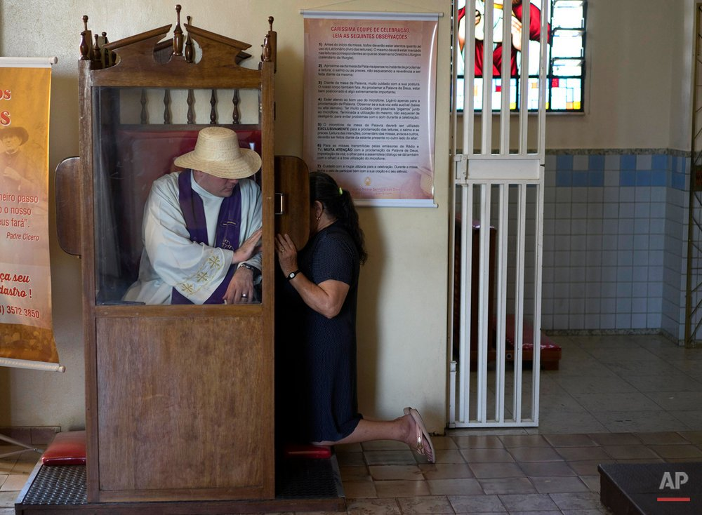 In this Oct. 30, 2015 photo, Priest Aureliano Godim listens a pilgrim's confession at Our Lady of Perpetuo Socorro church in Juazeiro do Norte, Brazil, during a week-long pilgrimage in honor of Padre Cicero. Pilgrims come to remember the man who is considered the patron saint of this city in Ceara state. (AP Photo/Leo Correa)