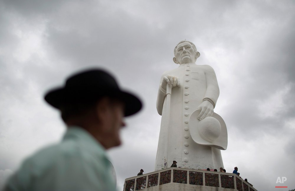 In this Oct. 31, 2015 photo, a statue of Padre Cicero, a late Brazilian priest who's venerated as a saint here but not recognized as one by the Roman Catholic Church, stands tall in Juazeiro do Norte, Brazil. People line up to touch the statue, some praying on their knees before it. Others leave letters of gratitude to him, who they credit with miracles. (AP Photo/Leo Correa)