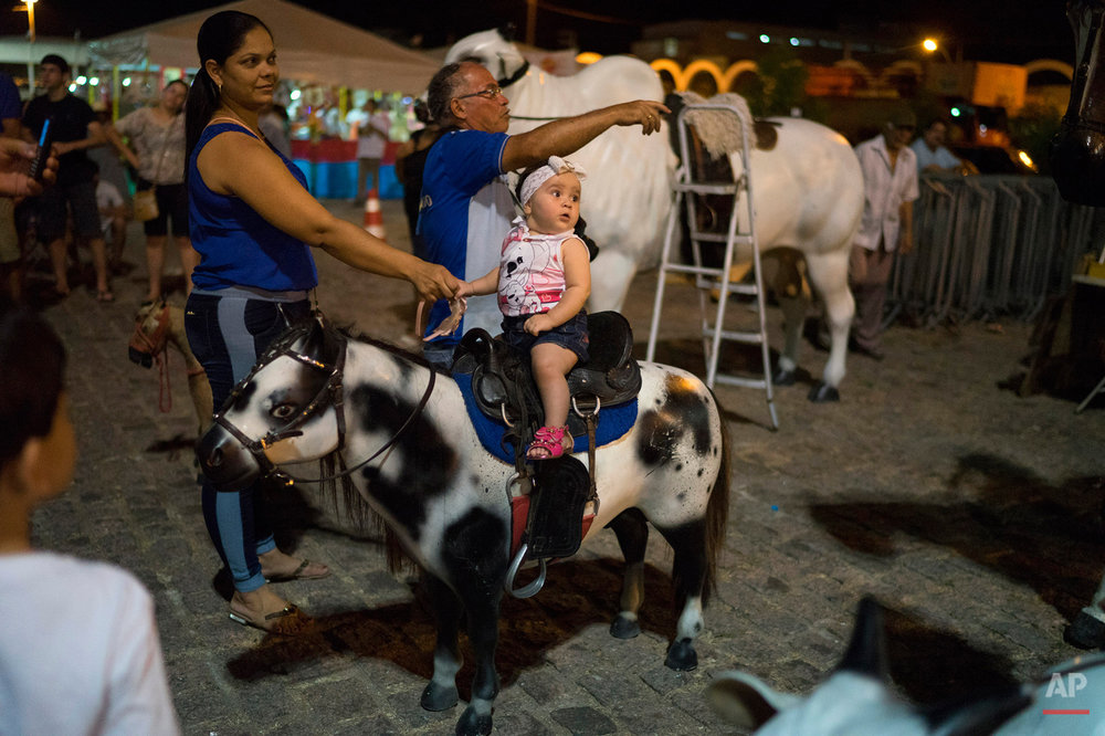 In this Oct. 30, 2015 photo, a child sits on a toy pony before having her portrait made in the square where a Mass will be held outside Our Lady of Sorrows Cathedral in Juazeiro do Norte, Brazil. For almost a week, including the Day of the Dead, the Brazilian city is filled with pilgrims who come to honor Padre Cicero, a figure venerated here as a saint but not recognized as one by the Roman Catholic Church. (AP Photo/Leo Correa)