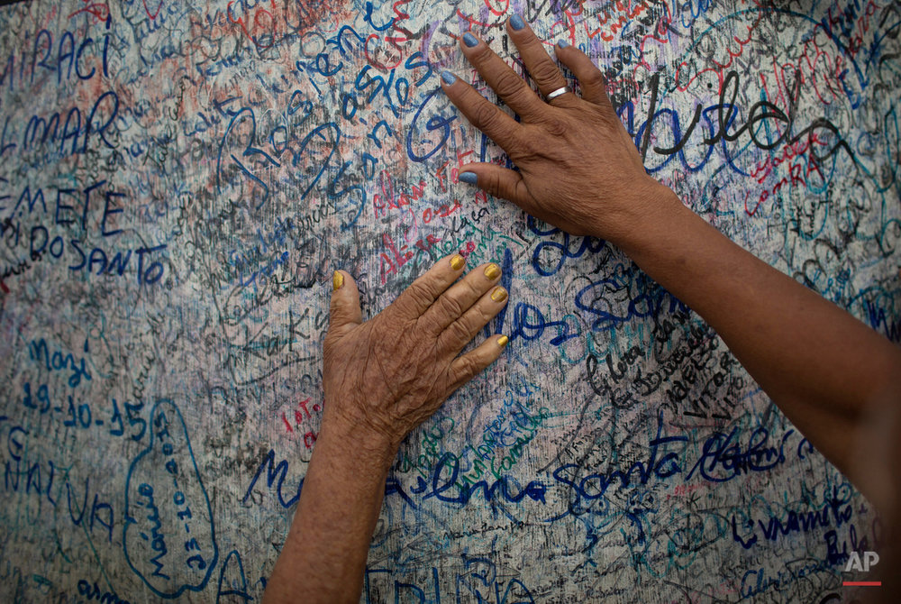 In this Oct. 31, 2015 photo, people touch the base of a large statue of Padre Cicero, covered in markings left by his followers in Juazeiro do Norte, Brazil, during an annual week long pilgrimage in his honor. Those who follow him say that during a Mass celebrated by the priest in 1889, a woman receiving communion declared that the Host had turned to blood in her mouth. (AP Photo/Leo Correa)