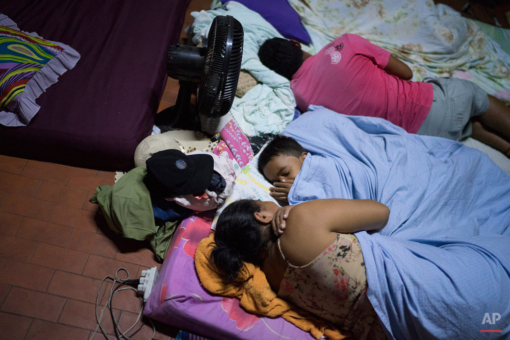 In this Oct. 30, 2015 photo, a family sleeps on a mattress at a shelter for pilgrims in Juazeiro do Norte, Brazil. The Brazilian city is filled for almost a week with pilgrims who come to honor Padre Cicero, a figure who became renowned for helping the poor and improving the lives of farmers and residents of Brazilís arid northeast. (AP Photo/Leo Correa)