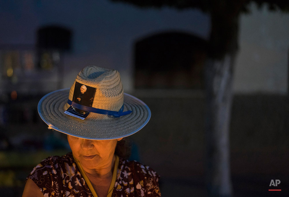 In this Oct. 30, 2015 photo, a pilgrim wearing a photo of Padre Cicero on her hat lights a candle in the square in Juazeiro do Norte, Brazil. Faced with Padre Cicero's persistent popularity, Pope Benedict XVI proposed that he be studied as a possible candidate for canonization. That review is still in progress, and his supporters hope that he will eventually be rehabilitated and canonized. (AP Photo/Leo Correa)