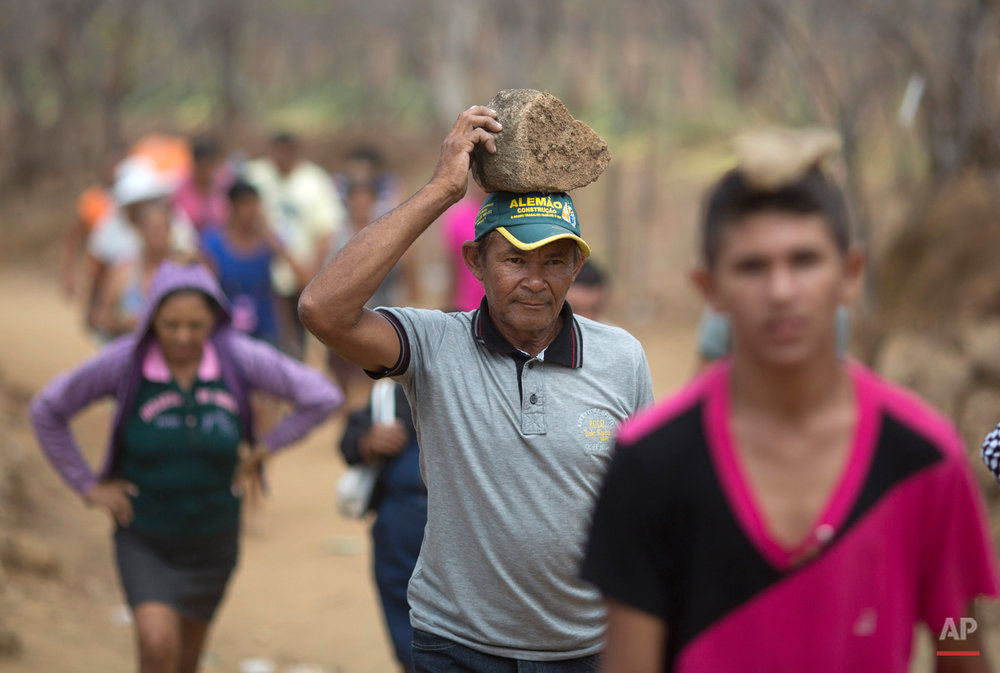 In this Nov. 1, 2015 photo, pilgrims balance rocks on their heads as they walk along the Holy Sepulchre path, a road used to pay back promises made to Padre Cicero, or to ask for favors, in Juazeiro do Norte, Brazil. Some pilgrims carry rocks on their heads as an extra sacrifice. (AP Photo/Leo Correa)