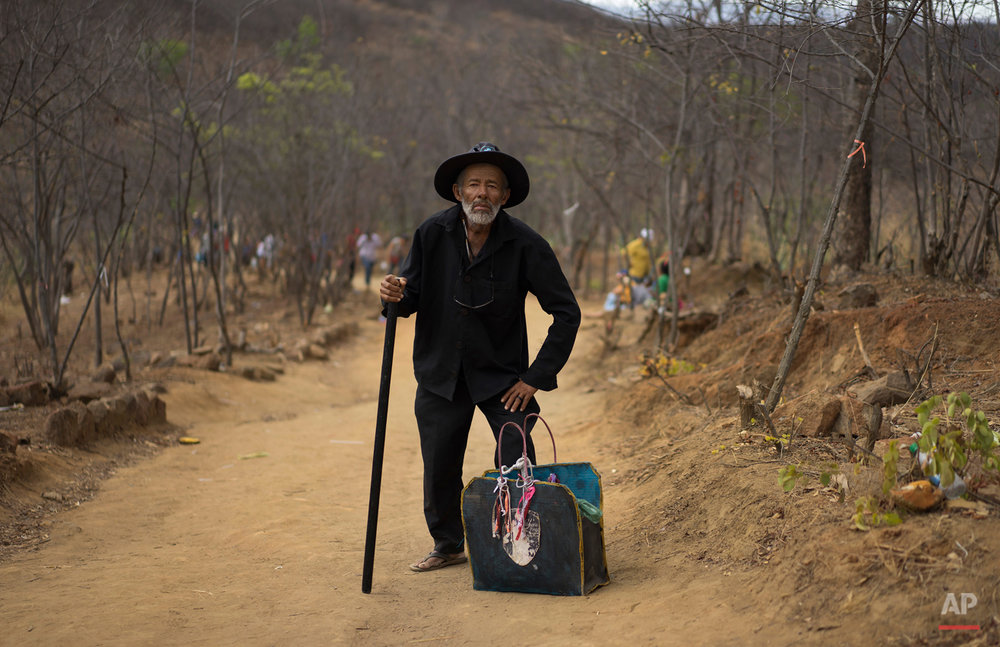 In this Oct. 31, 2015 photo, an elderly pilgrim using a walking stick poses for a portrait along the Holy Sepulchre path in Juazeiro do Norte, Brazil, during his pilgrimage to honor Padre Cicero. Followers of the late Brazilian priest visit each year for a five day period, wrapping up on Day of the Dead, to honor the man who is considered the patron saint of this city in Ceara state. (AP Photo/Leo Correa)