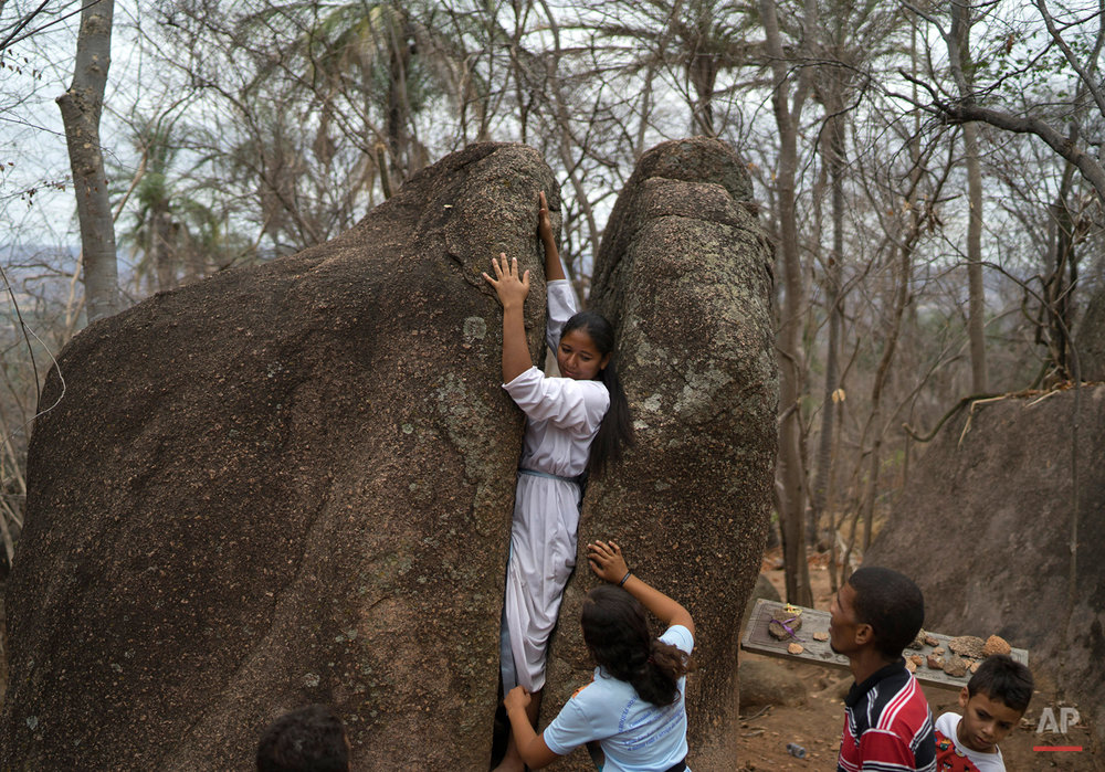 In this Nov. 1, 2015 photo, Zicelia Henrique dos Santos moves through the space of a cracked stone, along the Holy Sepulchre path used by pilgrims in Juazeiro do Norte, Brazil. The rock, called the Stone of Sin, is believed to bless those who pass through it. Henrique dos Santos, 28, said she's been making the pilgrimage to pay tribute to the late Brazilian priest ever since her mom asked Cicero to cure her from a childhood illness. (AP Photo/Leo Correa)