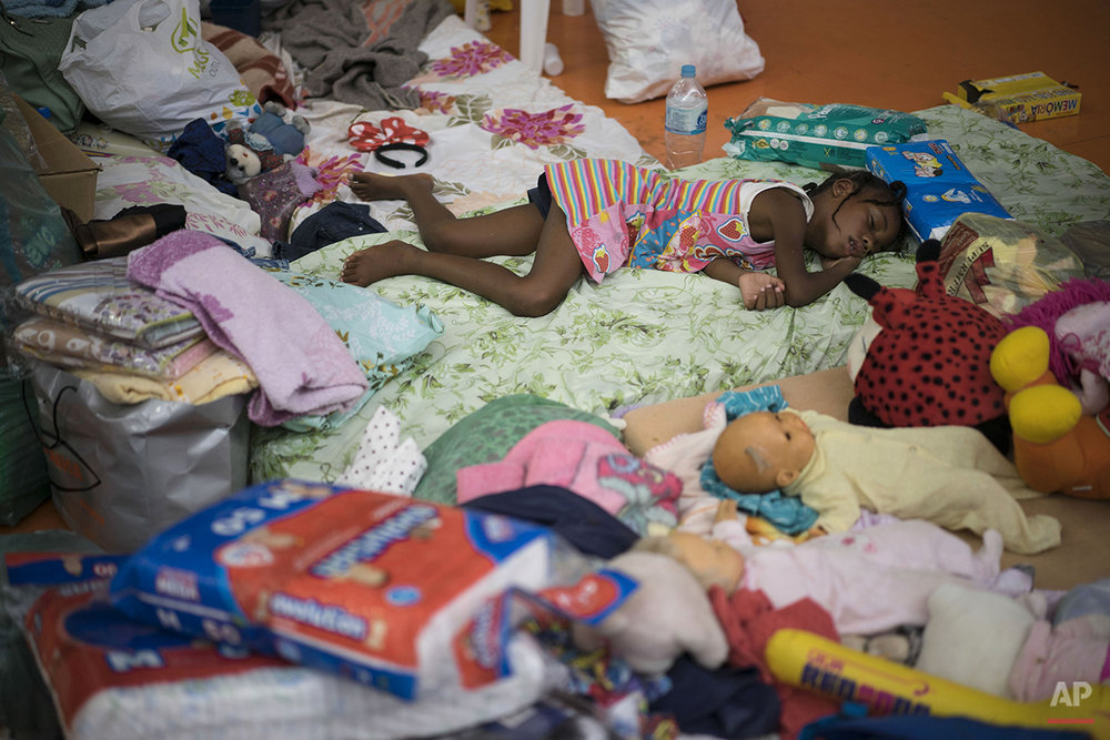 A girl rests on a mattresses in a sports arena after residents were displaced by dams that burst in Mariana, Minas Gerais state, Brazil, Friday, Nov. 6, 2015. The rupture of two dams at an iron ore mine unleashed a mix of water and mining residue on a village downhill, smothering the enclave of Bento Rodrigues. Only about 10 of the village's around 200 houses were left standing, and cars and other objects were tossed by what survivors described as an eruption of mud. The mine operator Samarco is jointly owned by the Brazilian mining company Vale and Australia's BHP Billiton. (AP Photo/Felipe Dana)
