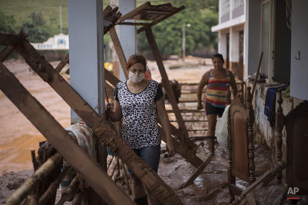 People stand in their damaged home in Barra Longa after a dam burst on Thursday in Minas Gerais state, Brazil, Saturday, Nov. 7, 2015. (AP Photo/Felipe Dana)