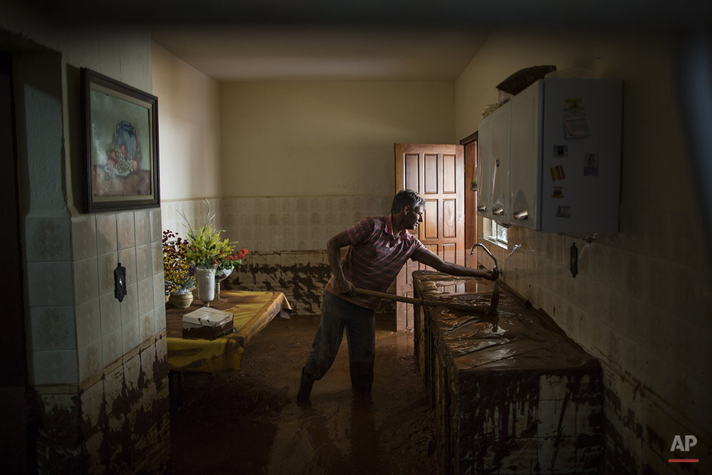 Antonio Carlos Carneiro removes mud from his damaged home in Barra Longa after a dam burst on Thursday in Minas Gerais state, Brazil, Saturday, Nov. 7, 2015. (AP Photo/Felipe Dana)