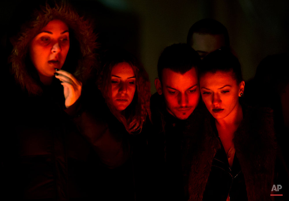 People, lit by burning candles, stand outside the compound that housed a nightclub where a fire occurred in the early Saturday in Bucharest, Romania, to pay respects to the victims, 24 hours after the accident Sunday, Nov. 1, 2015. Flames spread quickly through the crowded basement club, trapping many and triggering a stampede, making it the deadliest nightclub blaze in Romanian history. (AP Photo/Vadim Ghirda)