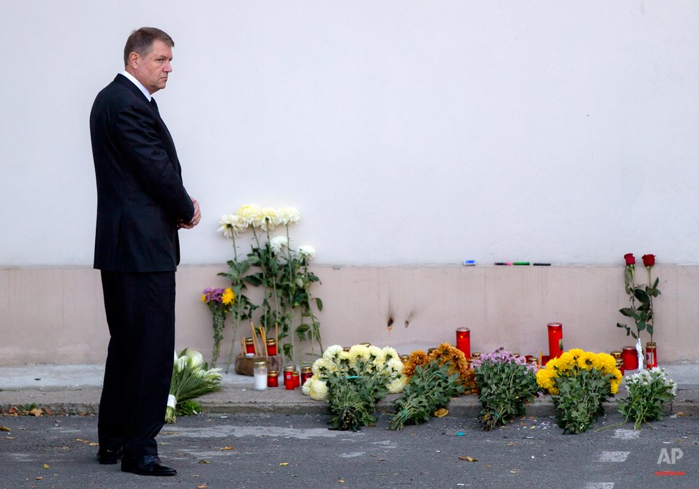 Romania's President Klaus Iohannis stands after placing flowers outside the compound that housed the nightclub where a fire occurred in the early morning hours in Bucharest, Romania, Saturday, Oct. 31, 2015. Hundreds of young people had gone clubbing at the hip Colectiv nightclub Friday night to enjoy a free concert by the Goodbye to Gravity metal band but the evening ended in horror, as the inferno caused a panic that killed tens of people and injured many others.(AP Photo/Vadim Ghirda)