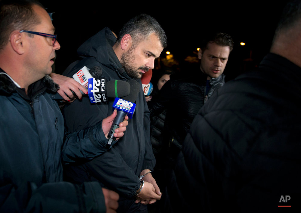 Costin Mincu, center, one of the owners of the Colectiv nightclub, exits the general prosecutor's office handcuffed in Bucharest, Romania, Monday, Nov. 2, 2015. The owners of the Colectiv nightclub were questioned by prosecutors Monday in connection with a fire that engulfed a nightclub Friday night, causing a stampede to a single exit door of the basement club and leaving tens of people dead and many more injured. (AP Photo/Vadim Ghirda)