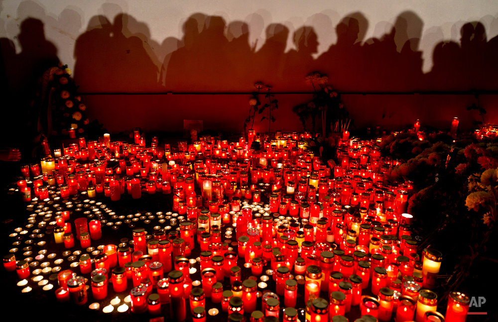 People cast shadows on a wall as they wait to light candles and lay flowers outside the compound that housed the nightclub where a fire occurred in the early morning hours in Bucharest, Romania, Saturday, Oct. 31, 2015. Hundreds of young people had gone clubbing at the hip Colectiv nightclub Friday night to enjoy a free concert by the Goodbye to Gravity metal band but the evening ended in horror, as the inferno caused a panic that killed tens of people and injured many others.(AP Photo/Vadim Ghirda)