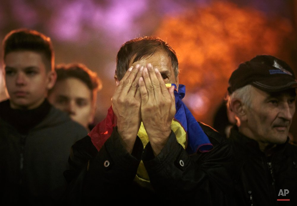 A man with a Romanian flag wrapped around his neck holds his palms in front of his face during the fourth day of protests, joined by tens of thousands across the country, calling for early elections, in Bucharest, Romania, Friday, Nov. 6, 2015. Large street protests followed the Oct. 30 nightclub fire, which many Romanians blame on a weak enforcement of regulations and corruption. The street protesters have condemned the nationís politicians as arrogant and corrupt and isolated from the problems of ordinary people. (AP Photo/Vadim Ghirda)