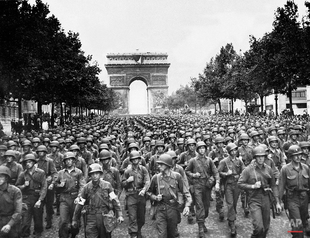 U.S. soldiers of Pennsylvania's 28th Infantry Division march along the Champs Elysees, the Arc de Triomphe in the background, on  Aug. 29, 1944, four days after the liberation of Paris, France. World War II began in September 1939 with Adolf Hitler's invasion of Poland. He launched the Holocaust and history's most destructive war, leaving 17,000,000 soldiers and 60,000,000 civilians dead. Germany surrendered on May 7, 1945. (AP Photo/Peter J. Carroll)