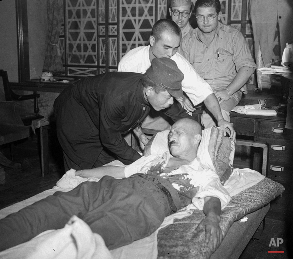 An unidentified Japanese is pictured making Gen. Hideki Tojo comfortable on a bed in his home as the former Premier of Japan grimaces from pain caused by a self-inflicted bullet wound September 11, 1945.  In the background, without a hat, is Russell Brines, AP correspondent.  The other man is unidentified.  (AP Photo/Charles Gorry)