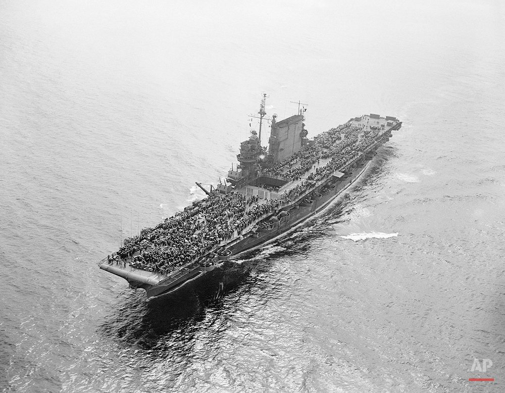 The USS Saratoga aircraft carrier with the US Pacific Fleet, sails through San Francisco's Golden Gate as part of the 3,800 crew crowds her flight deck on Sept. 13, 1945. (AP Photo/Ernest K. Bennett)