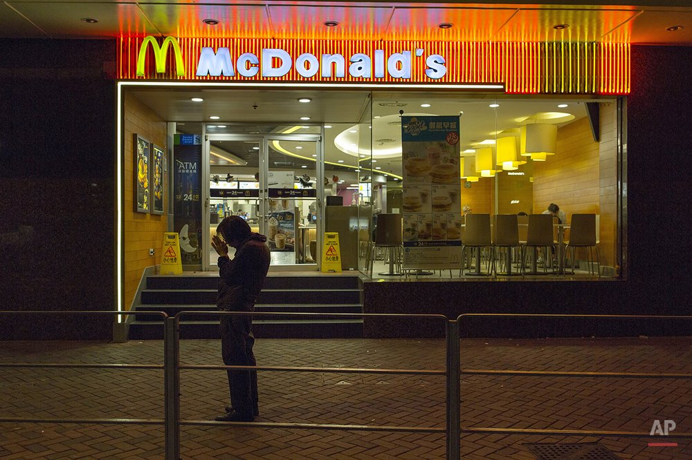 "In this Oct. 30, 2015 photo, a man, who has been sleeping at night in a 24-hour McDonald's branch in Hong Kong, prays outside the restaurant.in Hong Kong. The recent death of a woman at a Hong Kong McDonald's, where her body lay slumped at a table for hours unnoticed by other diners, has focused attention on the city's working poor and homeless people, dubbed ""McRefugees,"" who spend their nights at the fast food outlet's 24-hour branches. (AP Photo/Vincent Yu)"